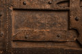 Old wood panel with iron studs and a decorative border of nails a weathered grunge natural brown surface in a full frame Royalty Free Stock Photo