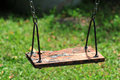 Old wood swing hanging in garden green background Stock Photography