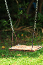 Old wood swing hanging in garden green background Stock Photo