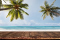Old wood table with blurred sea and coconut tree background Royalty Free Stock Photo