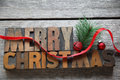 Old wood type merry christmas the words with red ribbon on an surface Stock Image