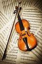 Old wood violin lying on musical notes Royalty Free Stock Images