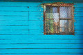 Old wooden blue house or barn with a barred small window Royalty Free Stock Photo