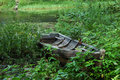 Old wooden boat in grass on the lake bank Royalty Free Stock Photo