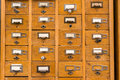 Old wooden card catalog with brass pulls and some yellowed blank paper labels Stock Images