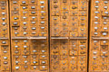 Old wooden card catalog with brass pulls and some yellowed blank paper labels Royalty Free Stock Photo