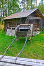 Old wooden cart in front of log barn Stock Photography