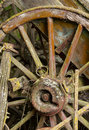Old wooden cartwheel against wood cart a ruined or buggy in detailed close up Royalty Free Stock Images