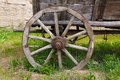 Old wooden cartwheel closeup with rusty steel rim and green grass Stock Images