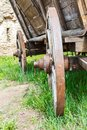 Old wooden cartwheel closeup with rusty steel rim and green grass Royalty Free Stock Photo