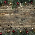 Old wooden Christmas background. Fir branches with baubles and gold stars. Space for text. Top view. Xmas square card Royalty Free Stock Photo