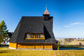 Old wooden church an with black roof during sunny autumn day Royalty Free Stock Images