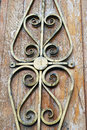 Old wooden church door decorated by rusty metallic ornament.