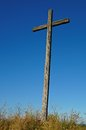 Old wooden cross against a blue sky background Royalty Free Stock Photo