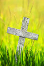 Old wooden cross simple with grass and meadow in background Stock Photos