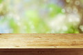 Old wooden deck table with spring bokeh background. Ready for product display montage. Royalty Free Stock Photo