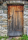 Old wooden door in field stone wall with rusty hinges and padlock Royalty Free Stock Photo
