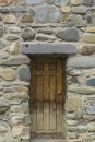 Old wooden door in the stone wall Royalty Free Stock Photo
