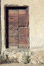 Old wooden door on stone wall of a house Royalty Free Stock Photo