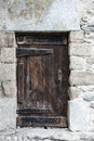 Old wooden door and stony wall with fashioned handle mounted in made of stones Royalty Free Stock Photography