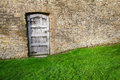 Old wooden door tall stone garden wall Stock Photo