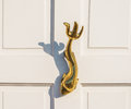 Old wooden door to house with a brass knocker in the shape of a Royalty Free Stock Photo