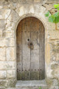 Old wooden doorway in provence arched inset into a stone wall france Stock Image