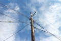 Old wooden electric pole against the blue sky Royalty Free Stock Photo