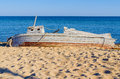 Old wooden fishing boat lying seashore clear sunny day fair weather blue sky Stock Photo