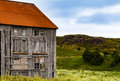An old wooden house in a field with flowers abandoned red orange roof and broken windows standing wild small hill and Stock Photo
