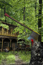 Old wooden house in the forest with a cart at the door closer to us a tree trunk with an ax nailed and traces of blood Stock Photography