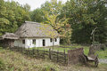 Old wooden house in the woods. Near the house, old horse-drawn , background Royalty Free Stock Photo