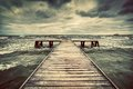 Old wooden jetty during storm on the sea. Dramatic sky with dark, heavy clouds Royalty Free Stock Photo