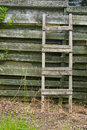 Old wooden ladder leaning on wooden slats weathered Royalty Free Stock Image