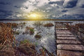 Old wooden pier with dry reed on sunset Royalty Free Stock Photo