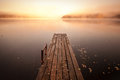 Old wooden pier on still lake with rising sun Royalty Free Stock Photos