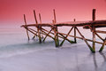 Old wooden pontoon under red sunset that is been hit by waves Royalty Free Stock Photography