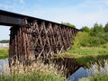 Old wooden railway trestle bridge spanning small river Royalty Free Stock Photo