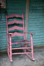 Old wooden rocking chair pink sitting on an outdoor porch Stock Image