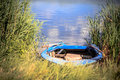 Old wooden rowboat on the shore of a river Stock Photos