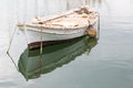 Old wooden rowing boat white weathered or dinghy moored in a harbour in greece Stock Image