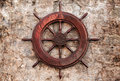 Old wooden ship steering wheel on stone wall Royalty Free Stock Image