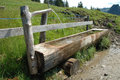 Old wooden trough filled with water standing at fence Stock Images