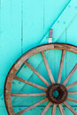 Old wooden wagon wheel against southwestern blue door Stock Photography