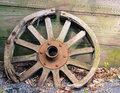 Old wooden wagon wheel leaning against wall Royalty Free Stock Photo