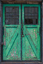 Old wooden warehouse door with a crane hook in front Royalty Free Stock Photo