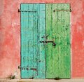 Old wooden weathered door painted on one side of turquoise and on the other green, with rusty lock and padlock. Pink wall peeled a Royalty Free Stock Photo