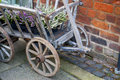 Old wooden wheel cart with heather plants in it detail the brick wall next to Royalty Free Stock Photo