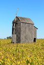 Old wooden windmill on a corn field Royalty Free Stock Photo