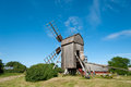 Old wooden windmill on the island in little village runsten oland sweden under a beautiful blue summer sky Royalty Free Stock Images